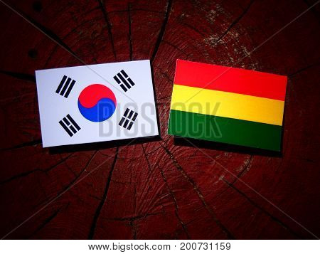 Bolivian Flag With South Korean Flag On A Tree Stump Isolated