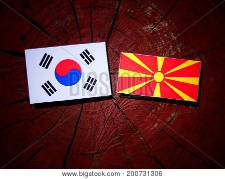 Macedonian Flag With South Korean Flag On A Tree Stump Isolated