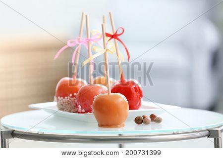 Plate with delicious candy apples on stand against blurred background