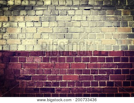 Faded Polish flag on an old brick wall background with a dark vignette