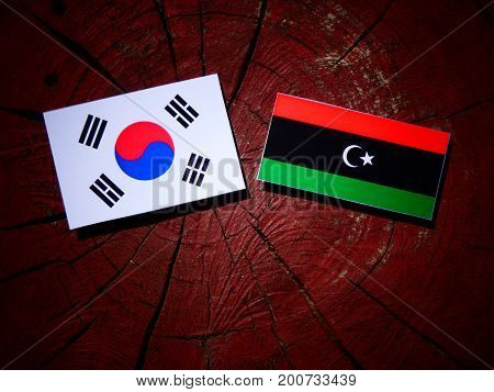 Libyan Flag With South Korean Flag On A Tree Stump Isolated