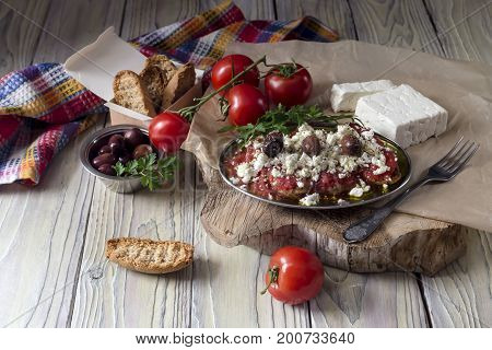 Crackers with grated tomatoes and feta cheese on a wooden table close up (Cretan cuisine)