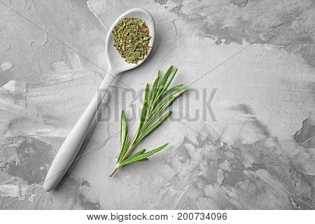 Spoon with dried herbs and fresh rosemary on grey background