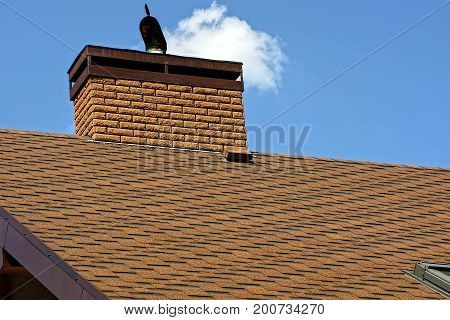 Brick chimney on a brown roof with tiles on a sky background
