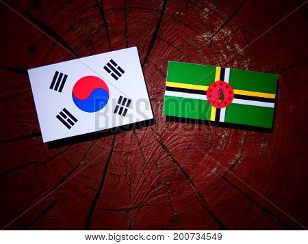 Dominica Flag With South Korean Flag On A Tree Stump Isolated