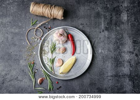 Composition with fresh rosemary and vegetables on metal plate