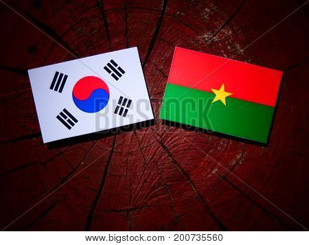 Burkina Faso Flag With South Korean Flag On A Tree Stump Isolated