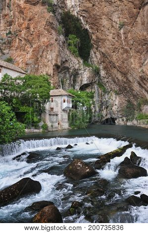 The Buna river with a waterfall flowing out of the cave as well as the tekkia - an ancient dervish home monks Blagaj Bosnia and Herzegovina poster
