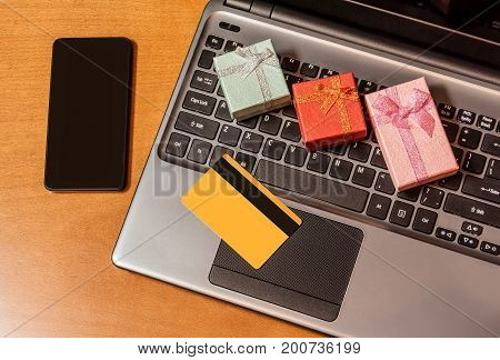 Gift boxes credit card on laptop keyboard. On-line shopping concept.