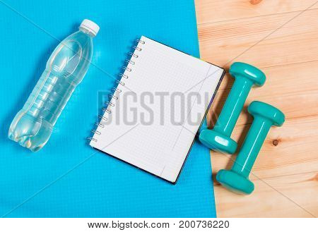 Bottle of water notebook and dumbbells on yoga mat
