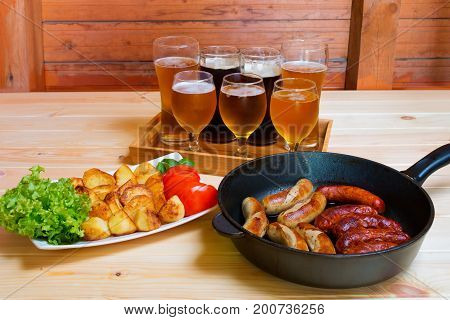 Mugs of beer and glasses of beer plate of roasted potato and frying pan with grilled sausages. Selective focus