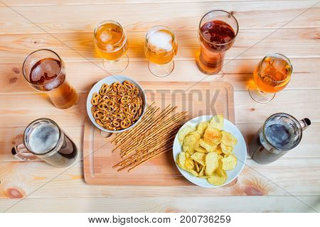 Beer mugs and glasses on wooden table. Beer snacks are chips salted straws and pretzels. Drink and snack for football match or party