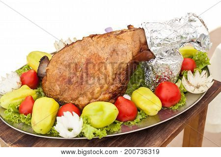 food, cooking, recipes and meal concept - closeup on a beautifully decorated oval dish with a huge delicious roasted piece of meat with fresh bell peppers and tomatoes to the perimeter, wooden table