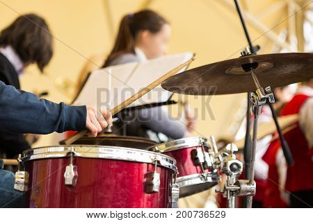 jazz band music performance concept - orchestra drum kit during the concert, closeup on hand of musician playing on percussion instruments and ride cymbal, selective focus