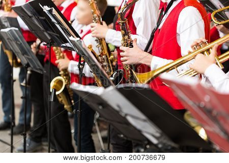 musical instrument, brass band and orchestra concept - closeup ensemble of musicians playing on trumpet and saxophone in red concert costumes, music stand, male hands with equipment, selective focus