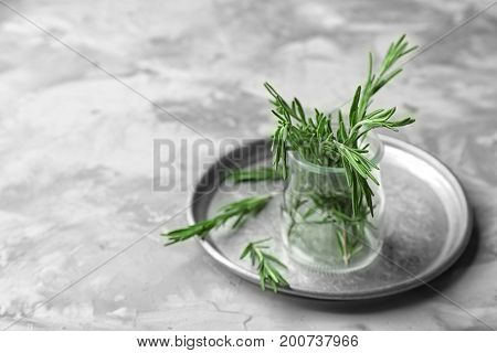 Jar with fresh rosemary on table