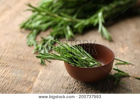 Bowl with fresh rosemary on table