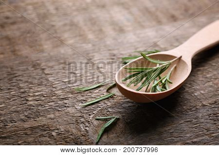 Spoon with fresh rosemary on wooden table
