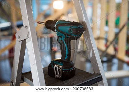 Portable Hand Drill On Ladder At Site