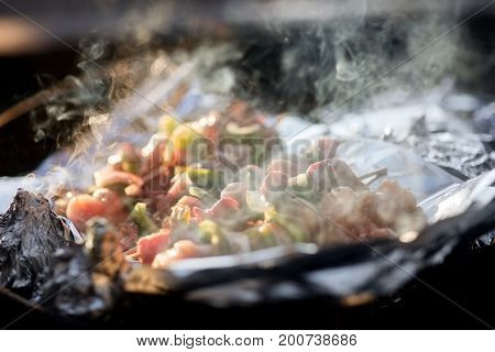 Smoke Rises From Meat Kebabs Grilling In Firepit