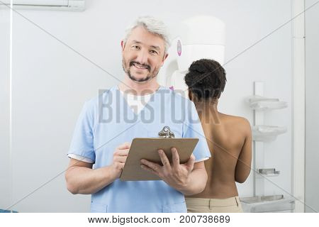 Doctor Holding Clipboard While Woman Undergoing Mammogram X-ray