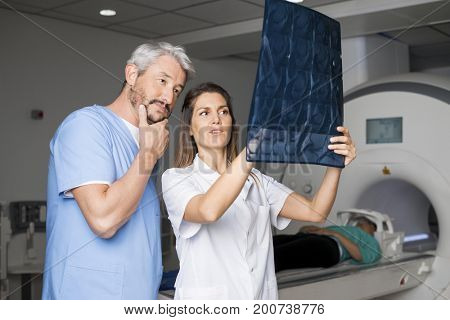Doctors Examining X-ray With Patient Lying On CT Scan Machine