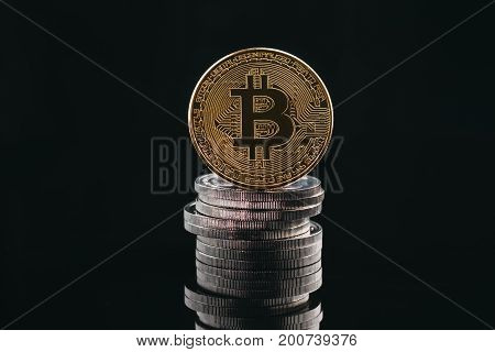 Pile of stacking coins with golden bitcoin on top king of all coins most valuable coin rising currency concept