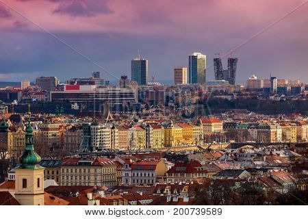 View of Old Town with colorful houses and red roofs and modern buildings on background in Prague, Czech Republic.