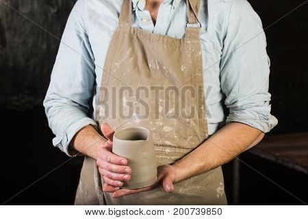 pottery, stoneware, ceramics art concept - closeup on master hands holding cup of unfired clay, young man in dirty apron stand at a workshop, male examines a fresh product before further processing