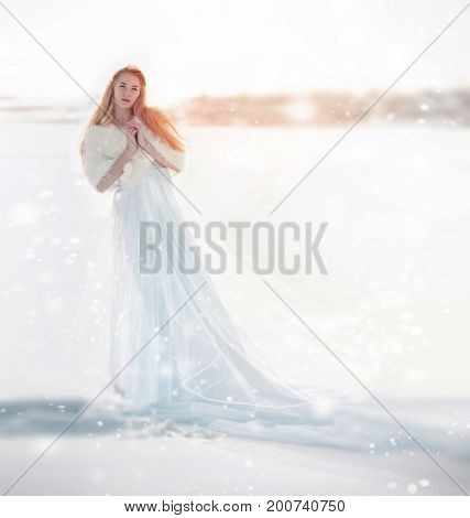 Snow fairy the snow Queen. Girl in a white dress standing in the snow wonderful way. Christmas fairy
