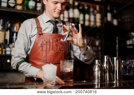 barman is pouring a coctail in a glass