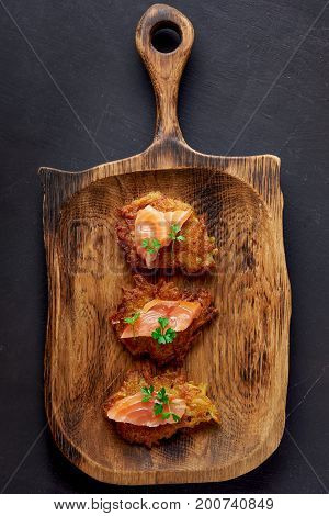 hash browns and salmon on wooden plate. top view