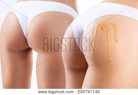 Honey flows down on woman buttocks. Massage concept. Anti-cellulite concept.