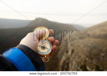 Point of view photo of explorer man searching direction with compass in his hand with blurred autumn mountains background