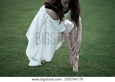 Ballerina in white dress on lawn background bent down to her feet.