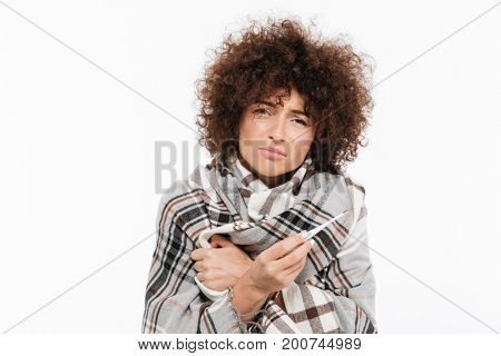 Sad sick woman standing wrapped in a blanket and holding thermometer isolated over white background