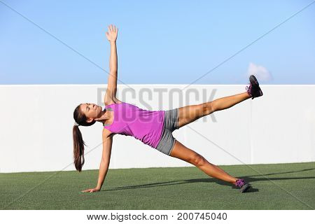 Yoga woman planking doing side plank leg lift core exercise at fitness gym class. Asian girl training side plank leg raise body core in yoga studio on home outdoor grass. Fitness gym lifestyle.