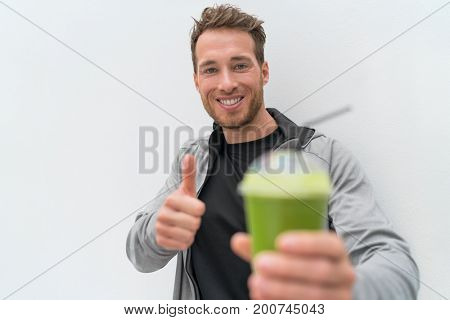 Happy healthy eating smoothie juice man thumbs up. Health food person drinking weight loss sport green smoothie drink. Fit nutrition lifestyle.