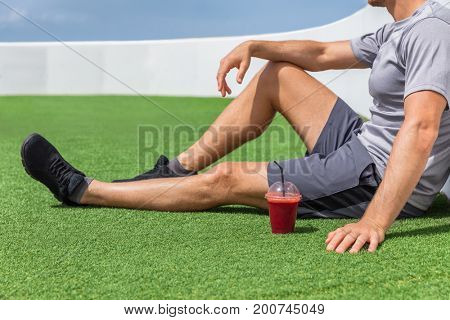 Juice smoothie sport man relaxing enjoying post workout morning breakfast sitting on outdoor grass at home or fitness gym. Athlete drinking red fruit smoothie drink.