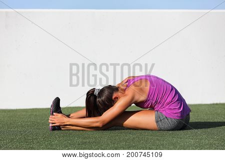 Yoga runner girl stretching back over legs doing seated Forward Bend. Fold named Paschimottanasana. Active woman doing sitting hamstring stretch warm-up exercises.
