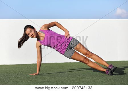 Side plank fitness woman training body core planking exercise. Workout at outdoor gym or home garden Asian girl exercising obliques abs muscles with yoga pose plank.