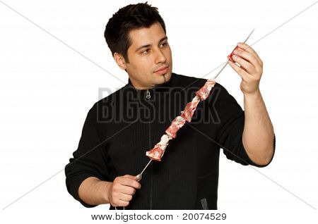 Young Man Putting Lamb Chops On A Skewer For Bbq