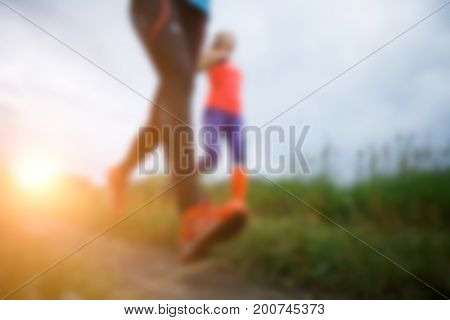 Image from bottom of two running female athletes in park, sunlight