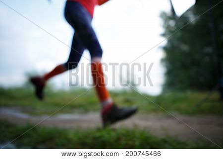 Blurred photo of running woman walking along path in park