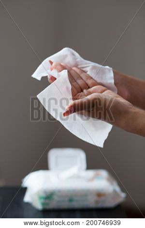 Woman clean hands with wet wipes, package in background