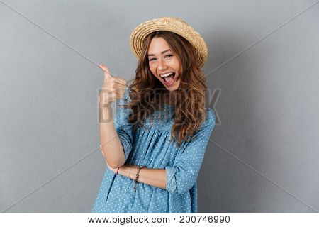 Picture of smiling young pretty woman standing over grey wall wearing hat showing thumbs up. Looking camera.