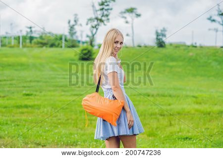 Young Woman Standing With Folded Inflatable Sofa In The Park. Lamzac