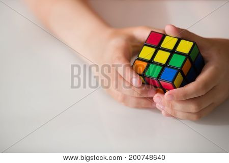 Moscow Russia August 16 2017: Rubik's cube in child's hands closeup. Boy holding Rubik's cube and playing with it.