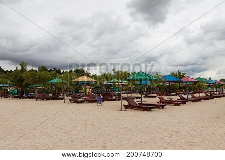 Empty Beach With Lots Of Sun Loungers And Umbrellas, Against The
