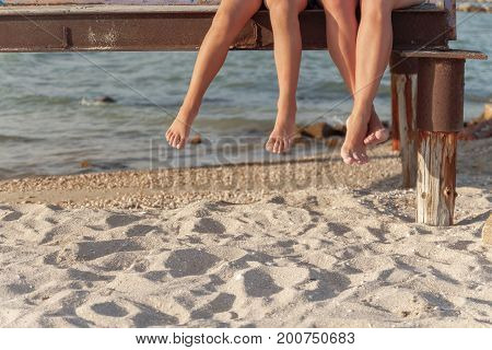 two pairs of legs dangling over the beach sand.